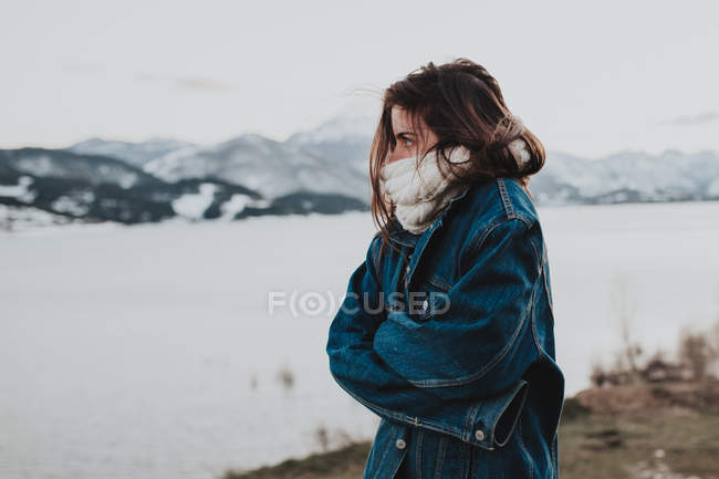 Brunette girl in scarf and denim jacket getting warm on winter riverside — Stock Photo
