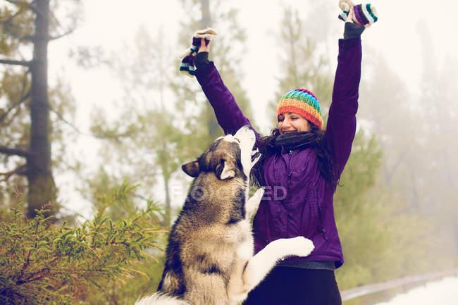 Сміється жінка грає з собакою в снігу — стокове фото