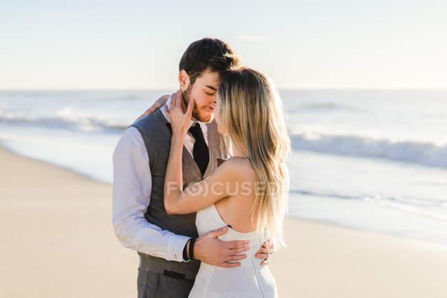Couple nuptial tendre s'embrassant au soleil à la plage — Photo de stock
