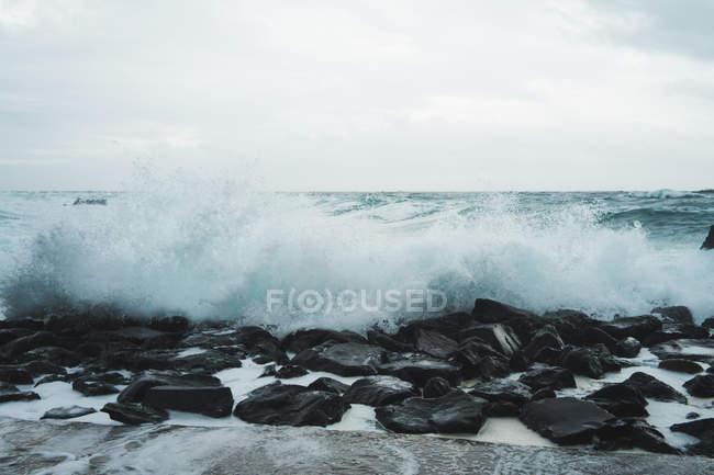 Волнистый океан катится по мокрому пирсу в облачный день . — стоковое фото