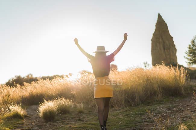 Vista posteriore della giovane donna in cappello che cammina nella natura con le braccia alzate — Foto stock