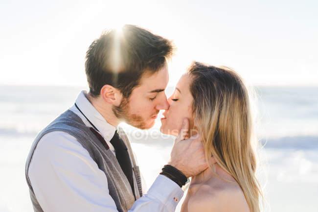Тендерна молодої пари цілуватися при сонячному світлі — стокове фото