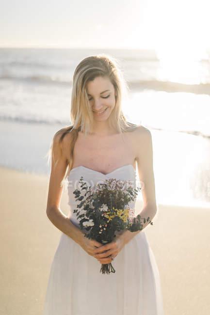Charmante junge Braut posiert mit Blumen am Strand — Stockfoto
