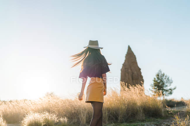 Rear view of young woman in hat walking in nature — Stock Photo