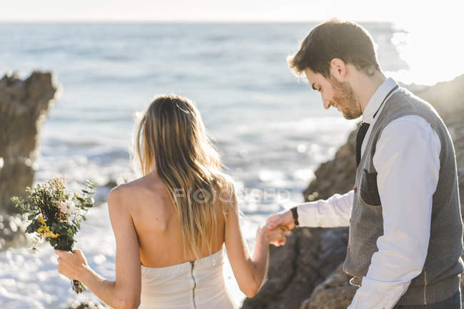 Sensual pareja de boda caminando en la costa - foto de stock