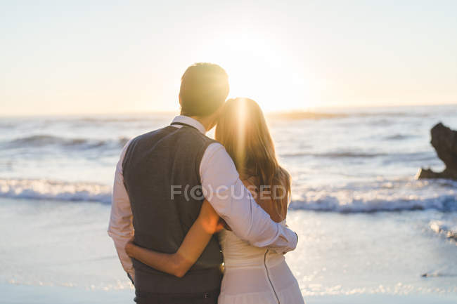 Back view of tender loving couple embracing and enjoying sunlight at seashore. — Stock Photo