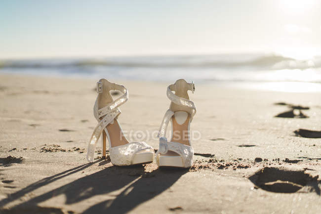 Lace shoes of bride in bright sunlight on sandy beach. — Stock Photo