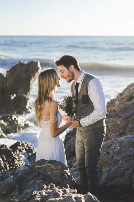 Sensual pareja de boda besándose en acantilados costeros en la costa - foto de stock