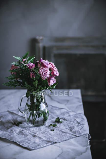 Куча розовых роз в стеклянной вазе на столе — стоковое фото