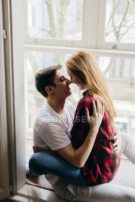 Junge sinnliche paar umarmt am Fenster — Stockfoto