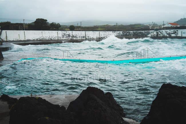 Paysage marin de l'océan ondulé et jetée humide sur la côte par temps nuageux . — Photo de stock