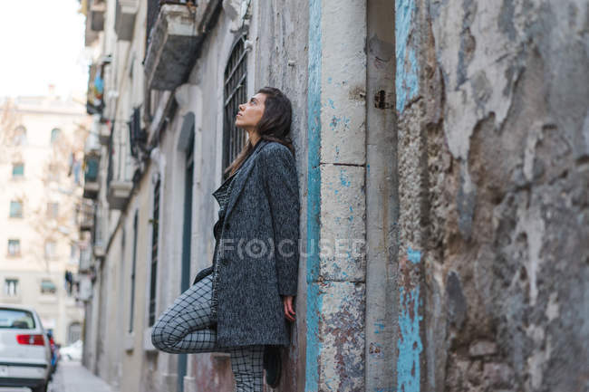 Young brunette woman leaning on grungy wall on street — Stock Photo