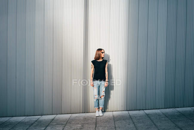 Stylish woman with tattoos standing on street at metallic wall. — Stock Photo