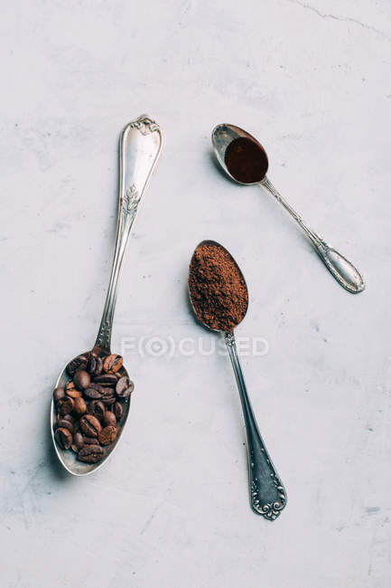 Directly above view of coffee beans and black coffee in retro spoons — Stock Photo