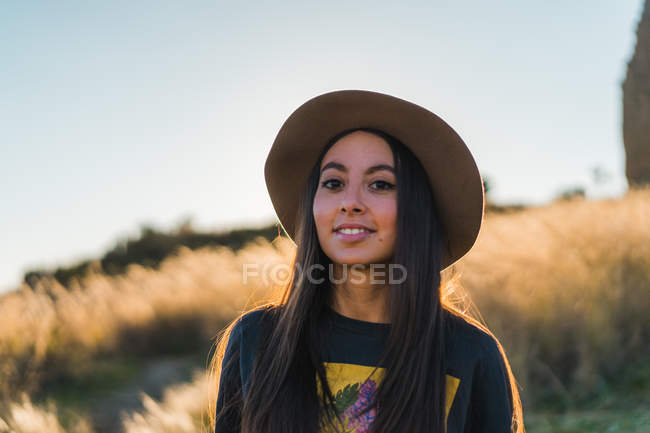 Smiling young woman in hat standing in nature and looking at camera. — Stock Photo