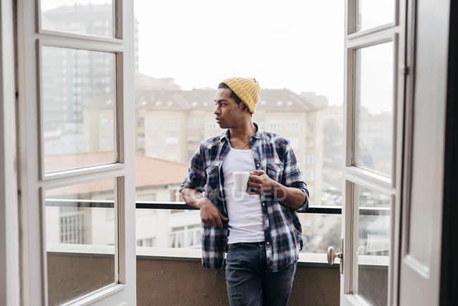 Stilvollen Mann Kaffeetrinken auf Balkon und Wegsehen — Stockfoto