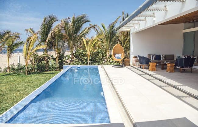 Exterior of villa with pool and loungers — Stock Photo