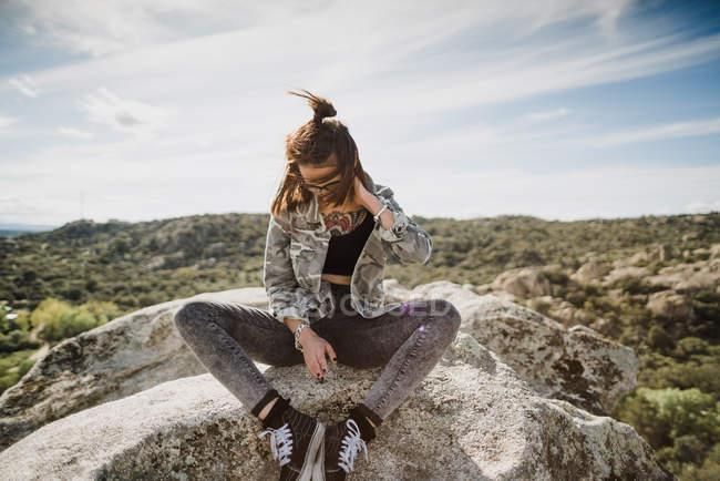 Junge Frau sitzt auf Klippe und schaut nach unten — Stockfoto