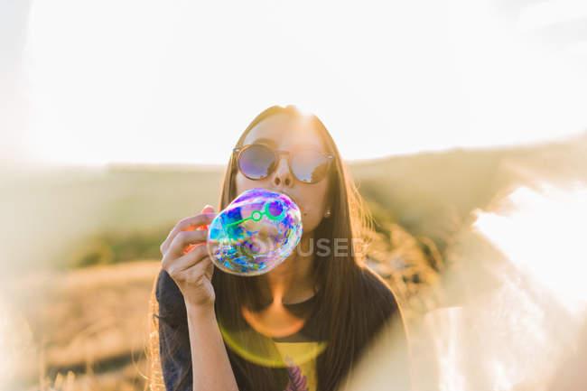 Mulher em óculos de sol soprando bolha de sabão na natureza — Fotografia de Stock