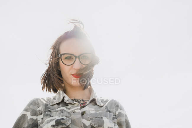 Thoughtful woman in glasses against sunny sky — Stock Photo