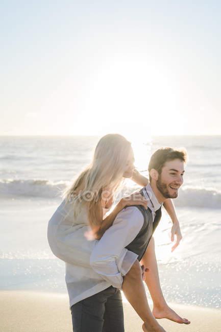Noivo carregando menina encantadora nas costas na praia ensolarada — Fotografia de Stock