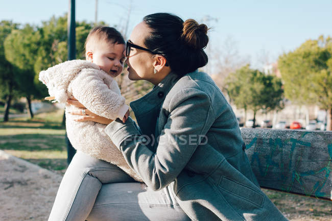 Cheerful woman playing with child in park — Stock Photo