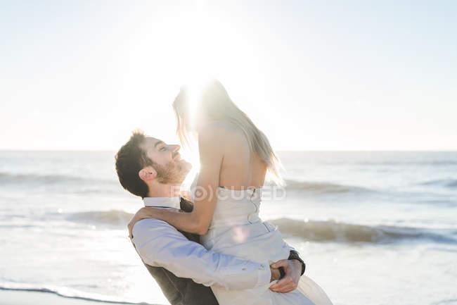 Веселый жених держит невесту на руках на солнечном пляже — стоковое фото