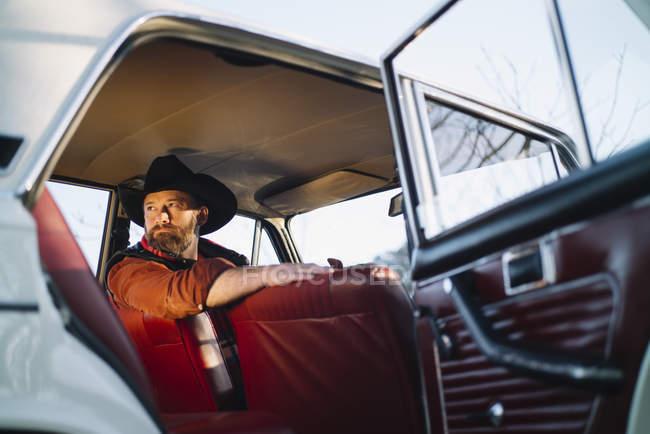 Hombre guapo mirando hacia atrás por encima del hombro en coche blanco - foto de stock
