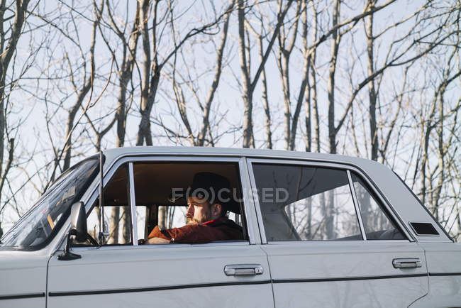 Bearded man in hat driving vintage white car in nature. — Stock Photo