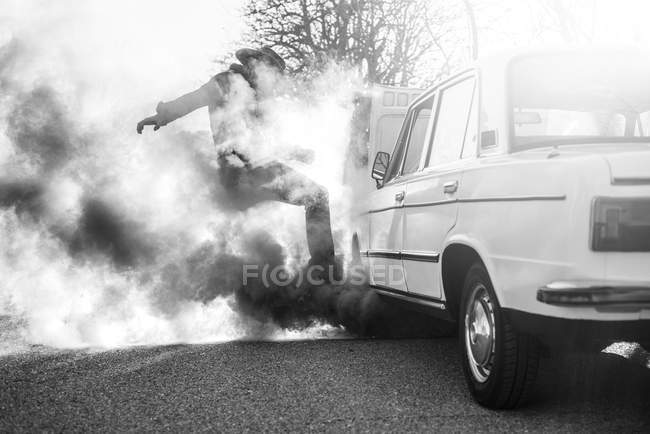 Man kicking broken vintage car emitting smoke on roadside. — Stock Photo
