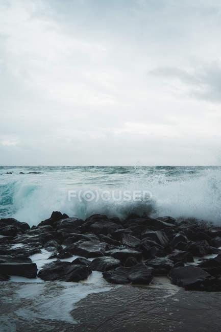Vue panoramique sur les rochers côtiers et les vagues océaniques par temps nuageux . — Photo de stock