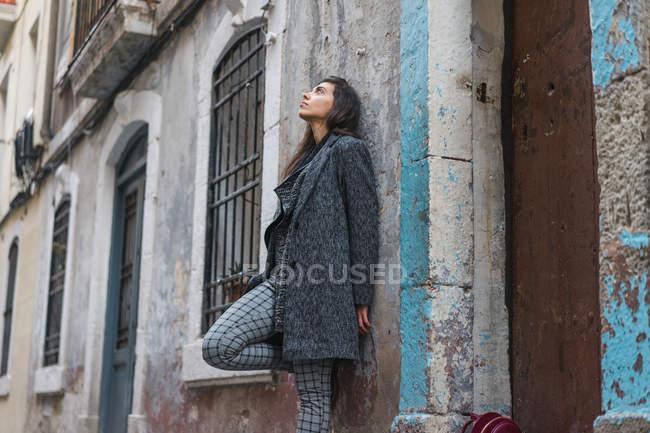 Junge Frau lehnt sich an grunzige Wand und schaut auf — Stockfoto