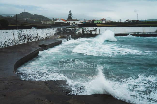 Océan ondulé et jetée humide sur la côte par temps nuageux . — Photo de stock