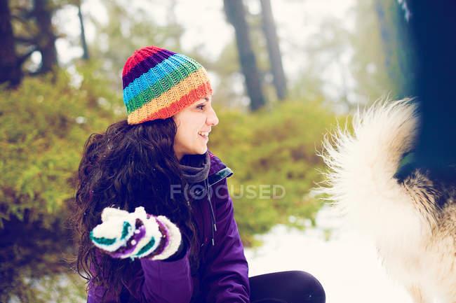 Mulher rindo, olhando para o cão na floresta de neve — Fotografia de Stock