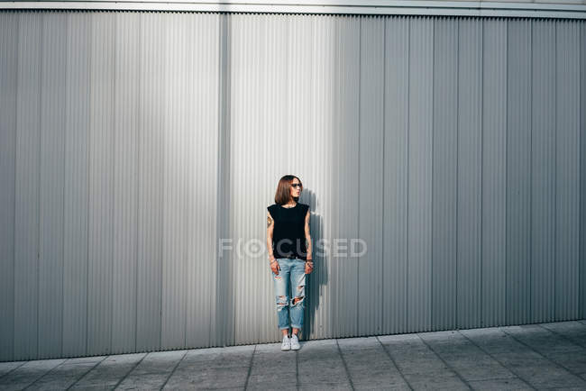 Elegante donna tatuata in occhiali da sole in posa a parete metallica — Foto stock