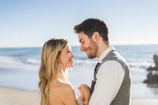 Нежная невеста смотрит друг на друга на пляже — стоковое фото