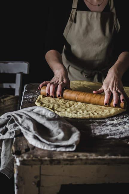 Femme de culture pétrir la pâte pendant la cuisson sur table rurale. — Photo de stock