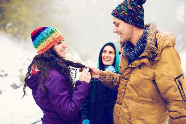 Cheerful friends having time in winter woods — Stock Photo