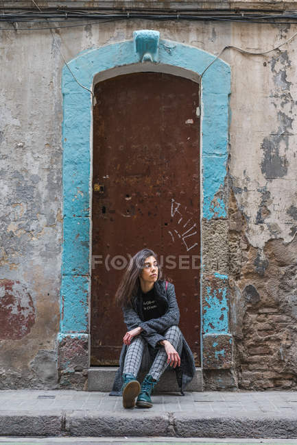Young woman sitting by grungy door at street — Stock Photo