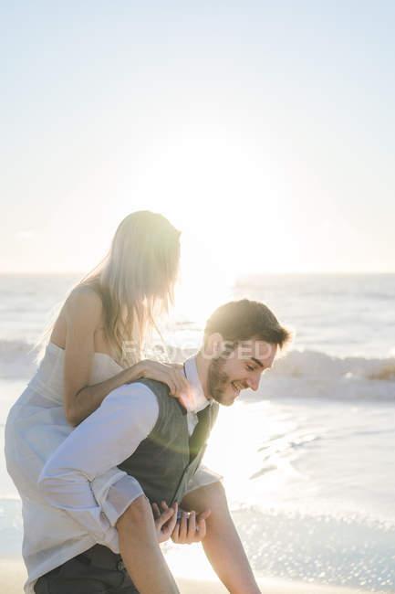 Noivo menina encantadora carregando nas costas na praia ensolarada — Fotografia de Stock