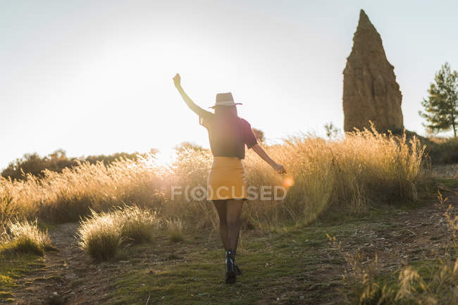 Cheerful woman in hat walking in nature and outstretching arms — Stock Photo