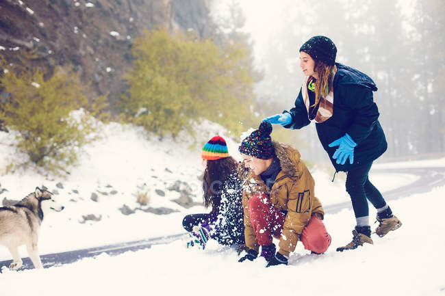 Group of friends playing snowballs with dog in woods — Stock Photo