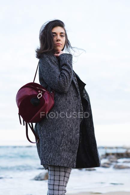 Stylish woman with backpack standing at ocean and looking at camera — Stock Photo