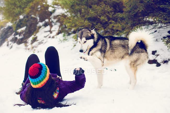 Mulher deitada na neve e brincar com o cão — Fotografia de Stock