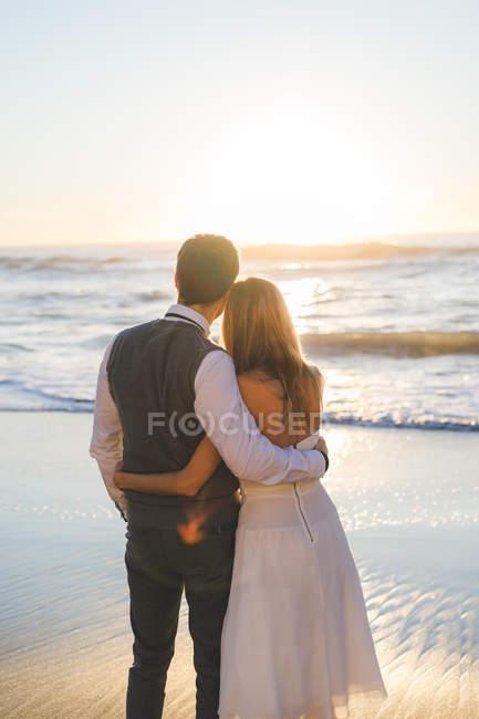Вид сзади на свадебную пару, обнимающуюся при свете заката на берегу моря — стоковое фото