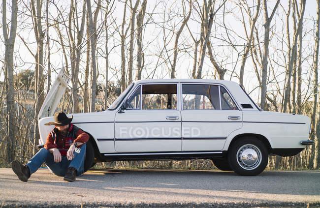 Homem de chapéu apoiado em carro vintage quebrado estacionado na beira da estrada . — Fotografia de Stock