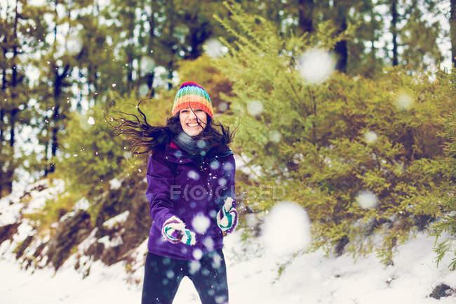 Donna sorridente che gioca le palle di neve nel bosco — Foto stock