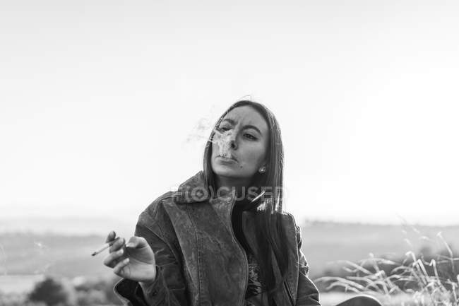Young  woman smoking cigarette in nature — Stock Photo