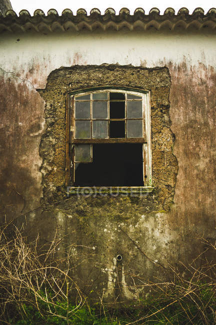 Broken window in dirty grungy wall of old building. — Stock Photo