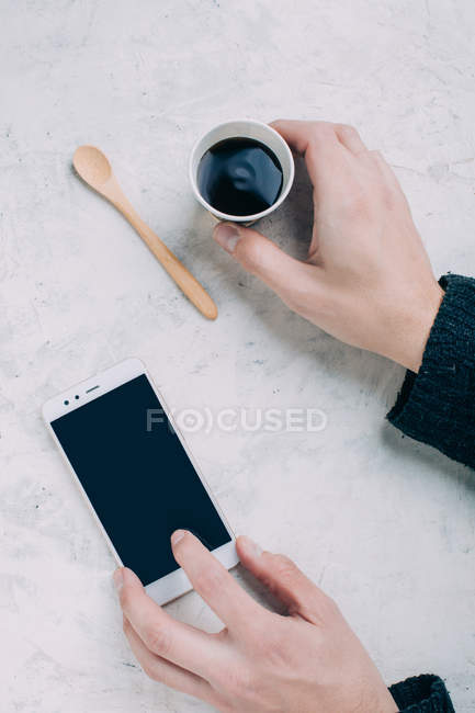 Ernte männliche Hände halten schwarzen Kaffee in Einweg-Cup und smartphone — Stockfoto